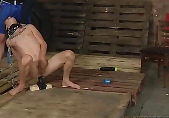Chained gay slave shoves a giant dildo up his ass for master