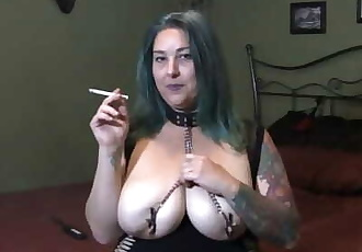 Chastity smokes wearing a collar and nipple clamps
