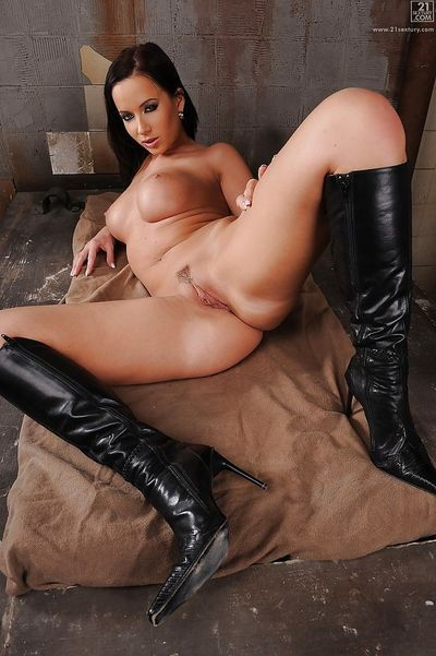 Brunette babe Cindy Dollar struts in black boots and hot pants in dungeon