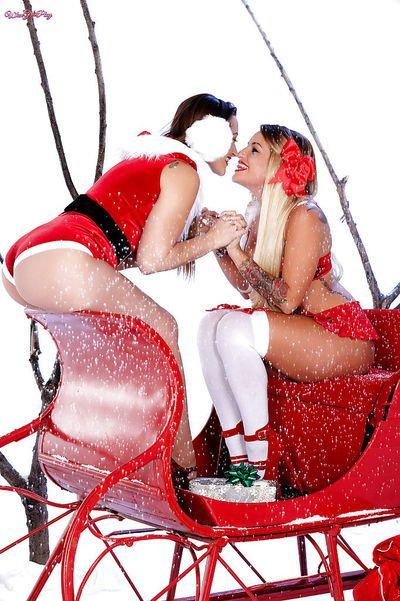 Stocking clad lesbian pornstars Dani Daniels and Kissa Sins kissing at Xmas