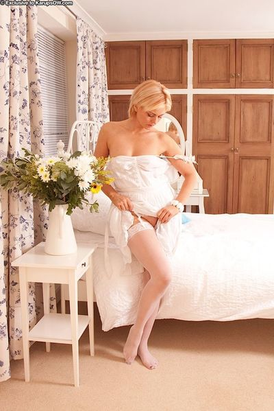 Older blonde lady Rebecca removing lingerie before rolling off white stockings