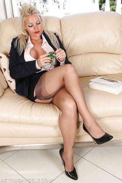 Curvy blonde lady in pantyhose flashing thigh and garters while smoking